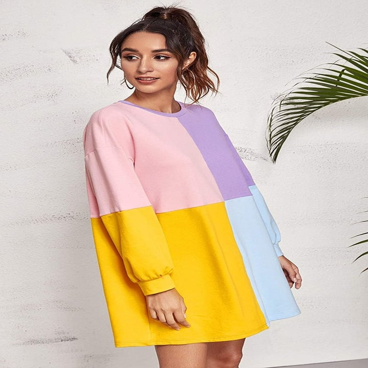 A model wearing the long-sleeve pink, yellow, blue, and lavender dress