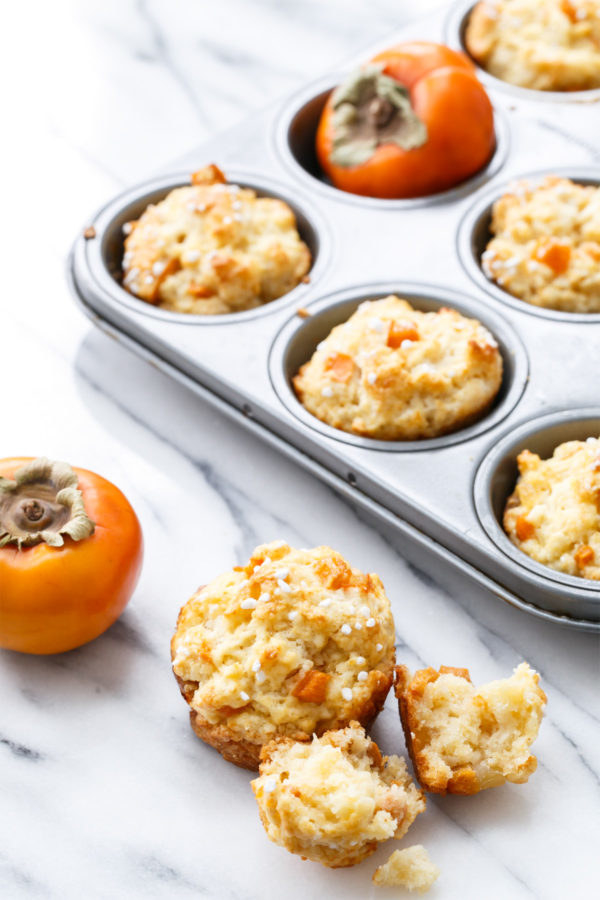 A muffin tray filled with ginger persimmon scone muffins and one crumbled muffin on the side.