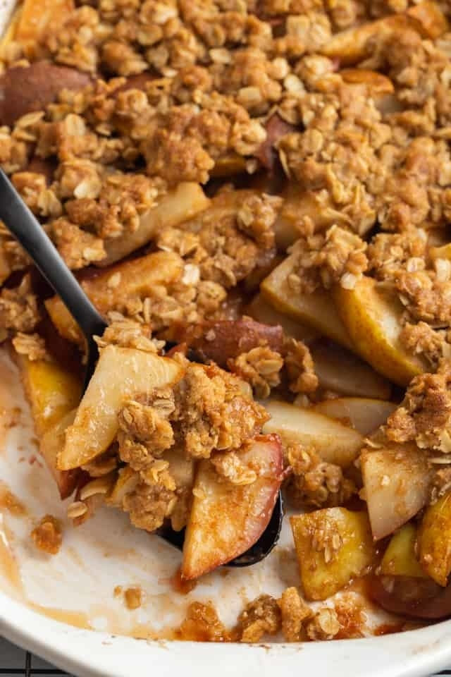 A baking dish filled with pear and apple crumble.