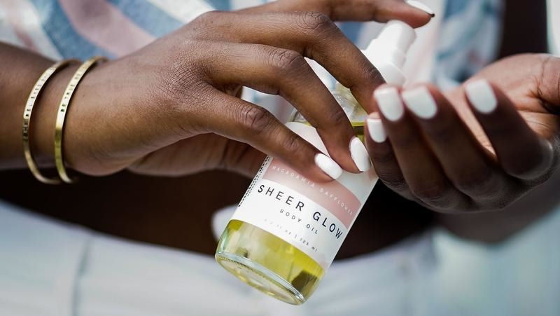 Hands applying The London Grant Co. Sheer Glow Body Oil.
