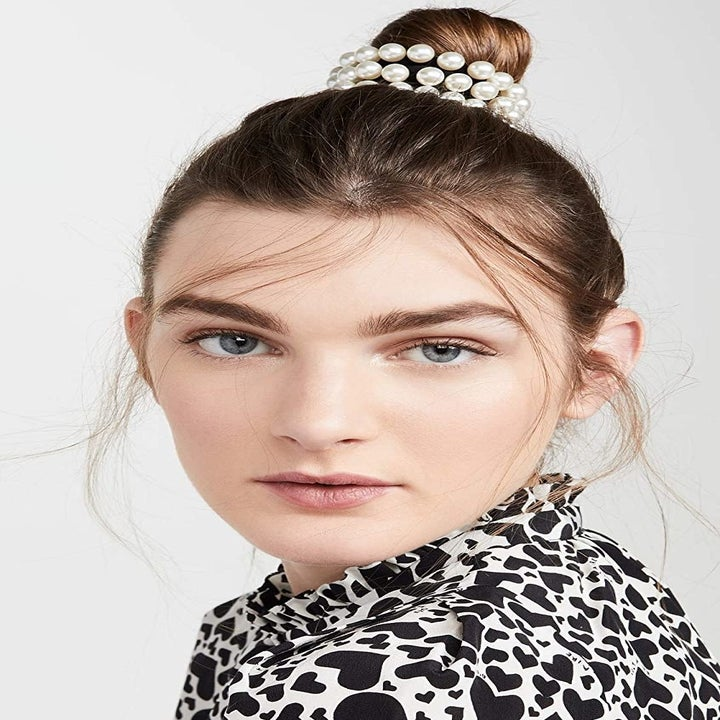 A model with the three ties stacked together on a bun in their hair