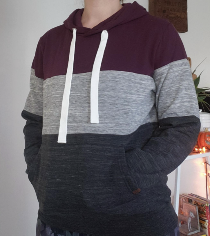 Reviewer wearing multicolored pullover hoodie