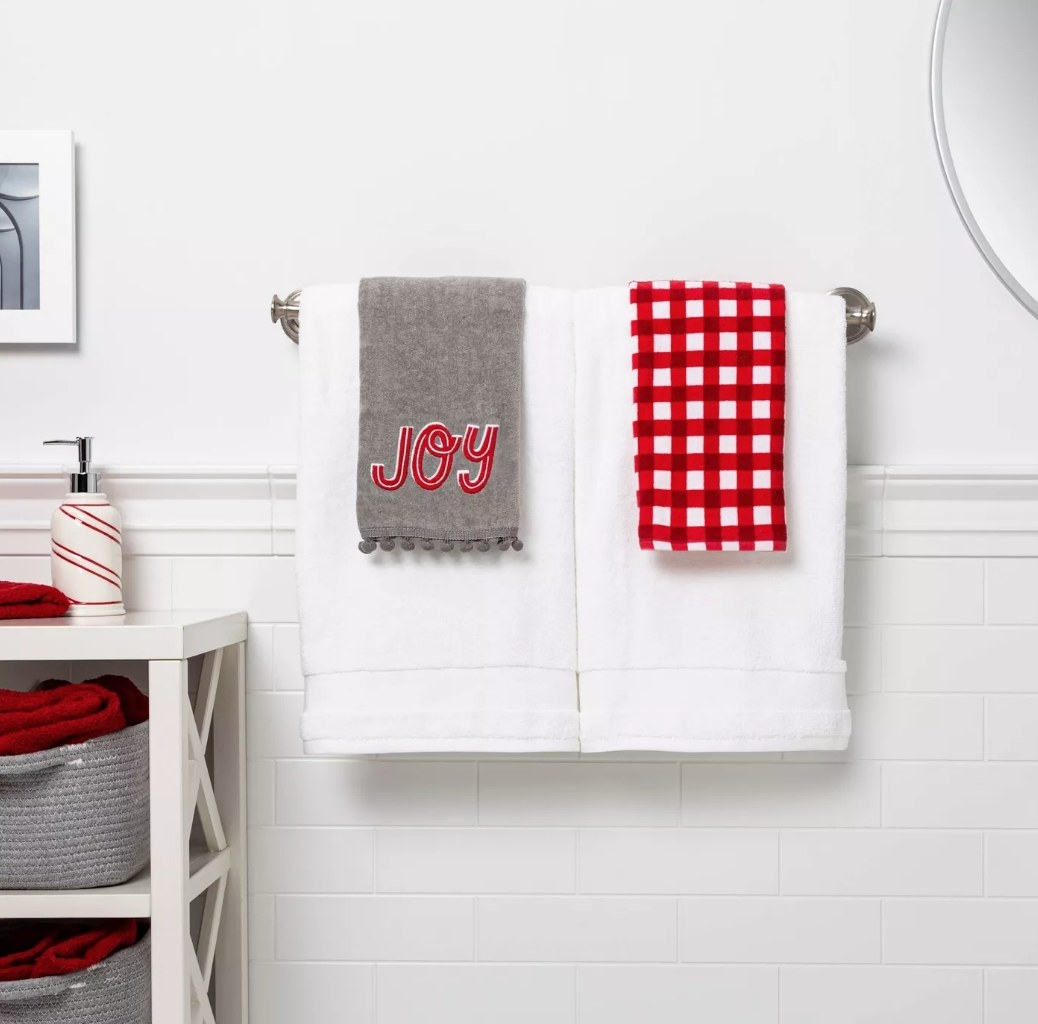 """Gray hand towel with """"joy"""" in red writing next to red and white plaid hand towel"""