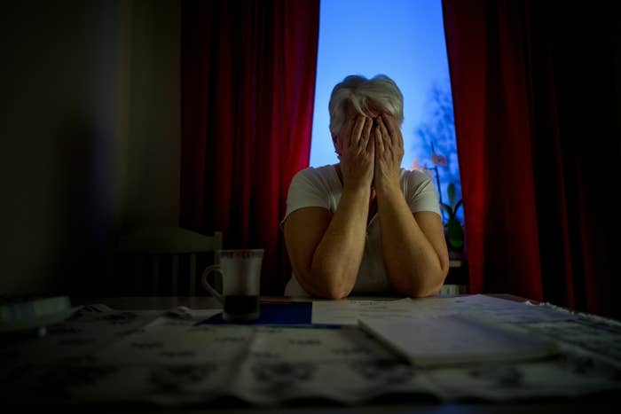 A woman sits in front of a window with her head in her hands