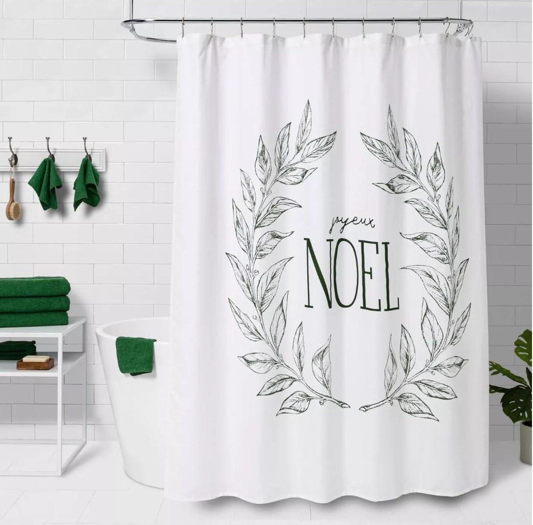 """White shower curtain that says """"joyeux noel"""" in green lettering"""