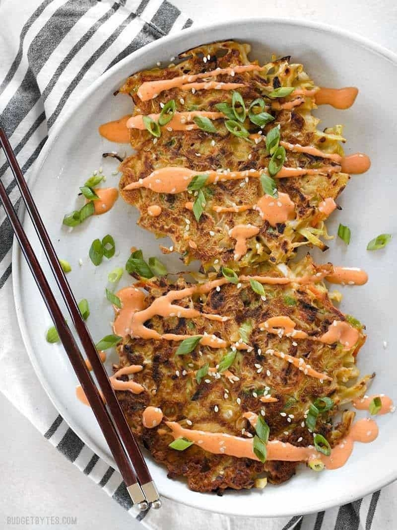 A Japanese-inspired cabbage pancake on a plate with spicy mayo drizzled on top.