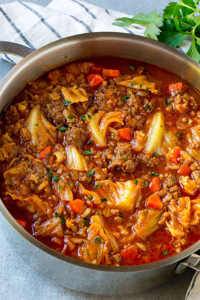 A bowl of cabbage soup with sausage and carrots and diced tomatoes.