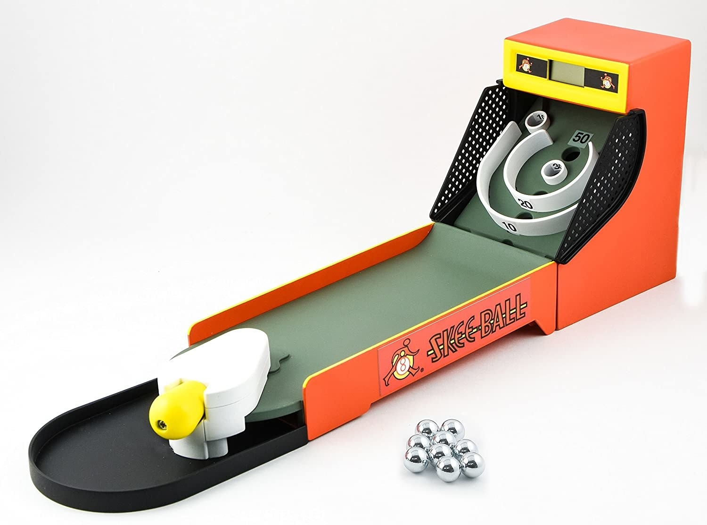 Mini skee-ball game next to nine silver balls