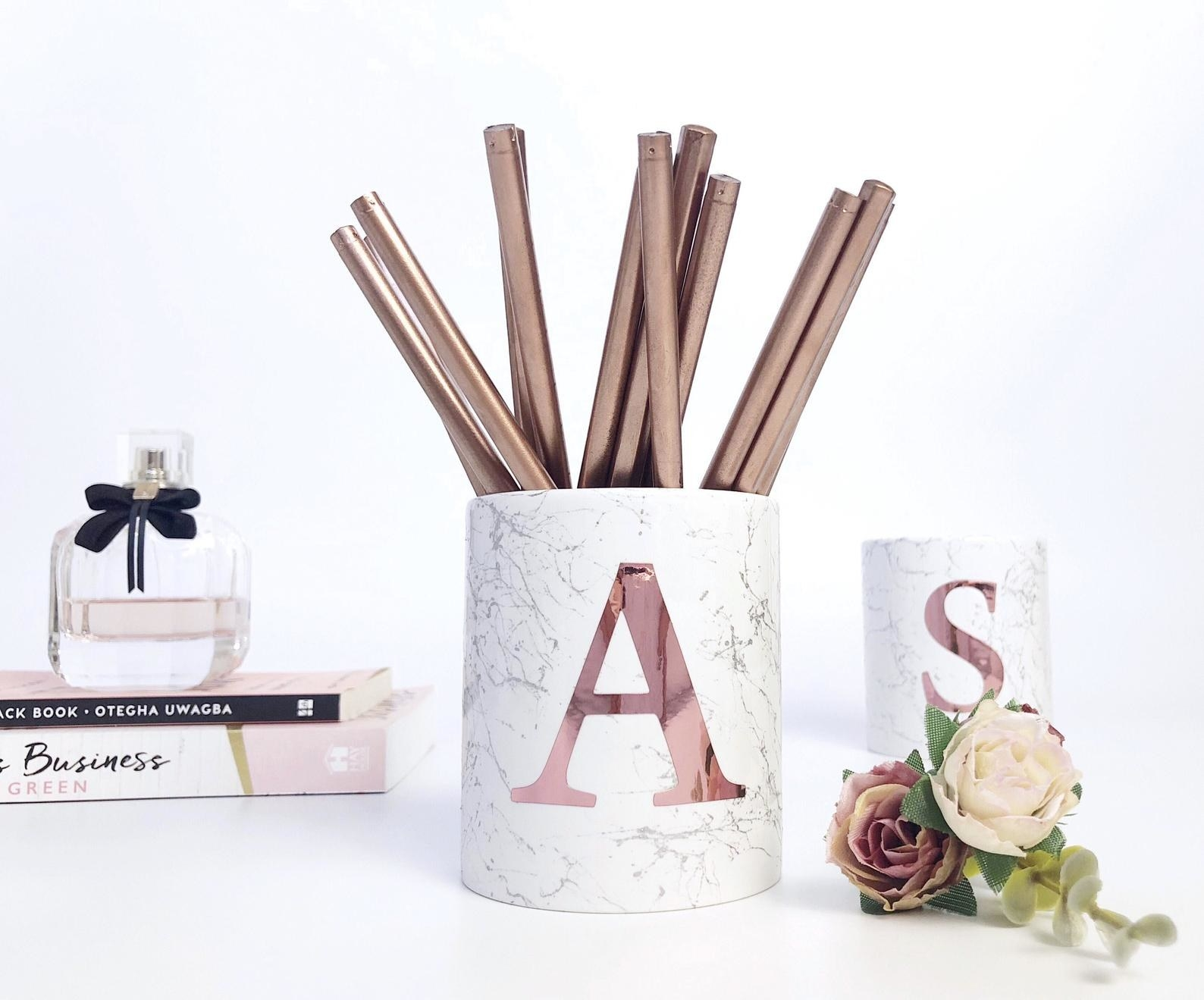 Monogram pencil cups filled with pens placed on table