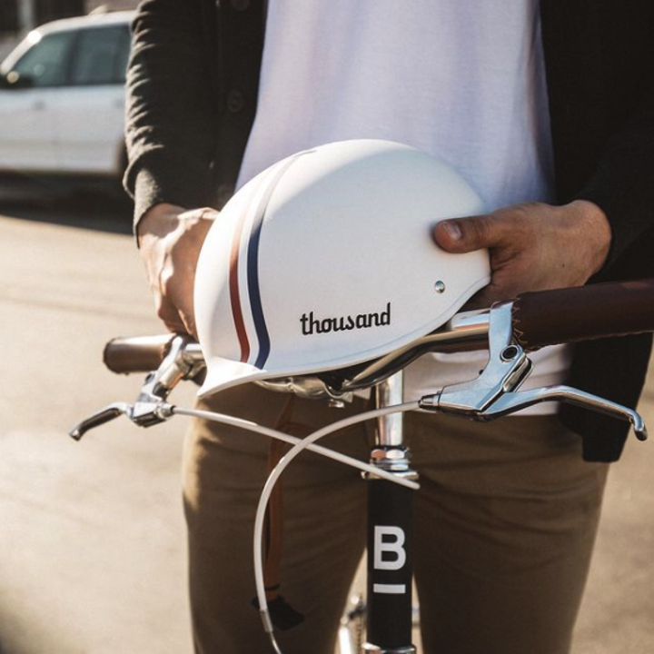 A close-up of someone holding the bike helmet while sitting on a bike
