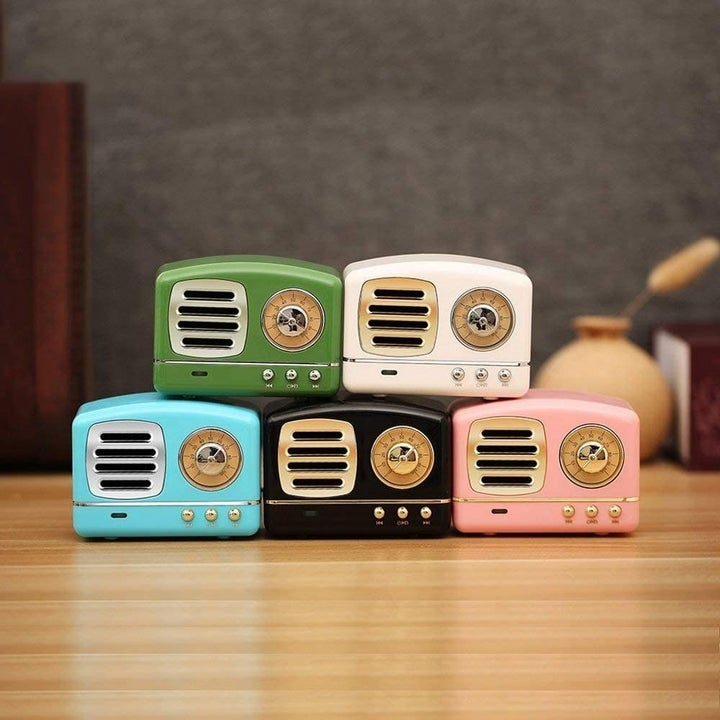 Five retro-style mini Bluetooth speakers placed on a table