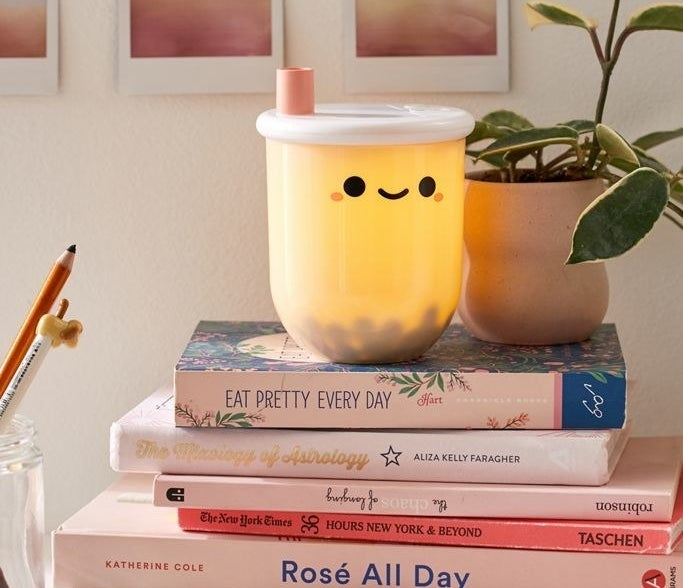 Mini boba tea-shaped lamp placed on a stack of books