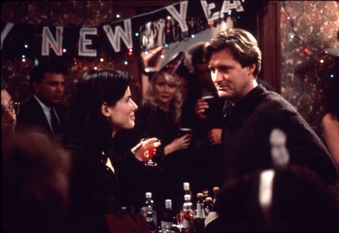 Still from While You Were Sleeping: Sandra Bullock and Bill Pullman face each other smiling while attending a new years eve party