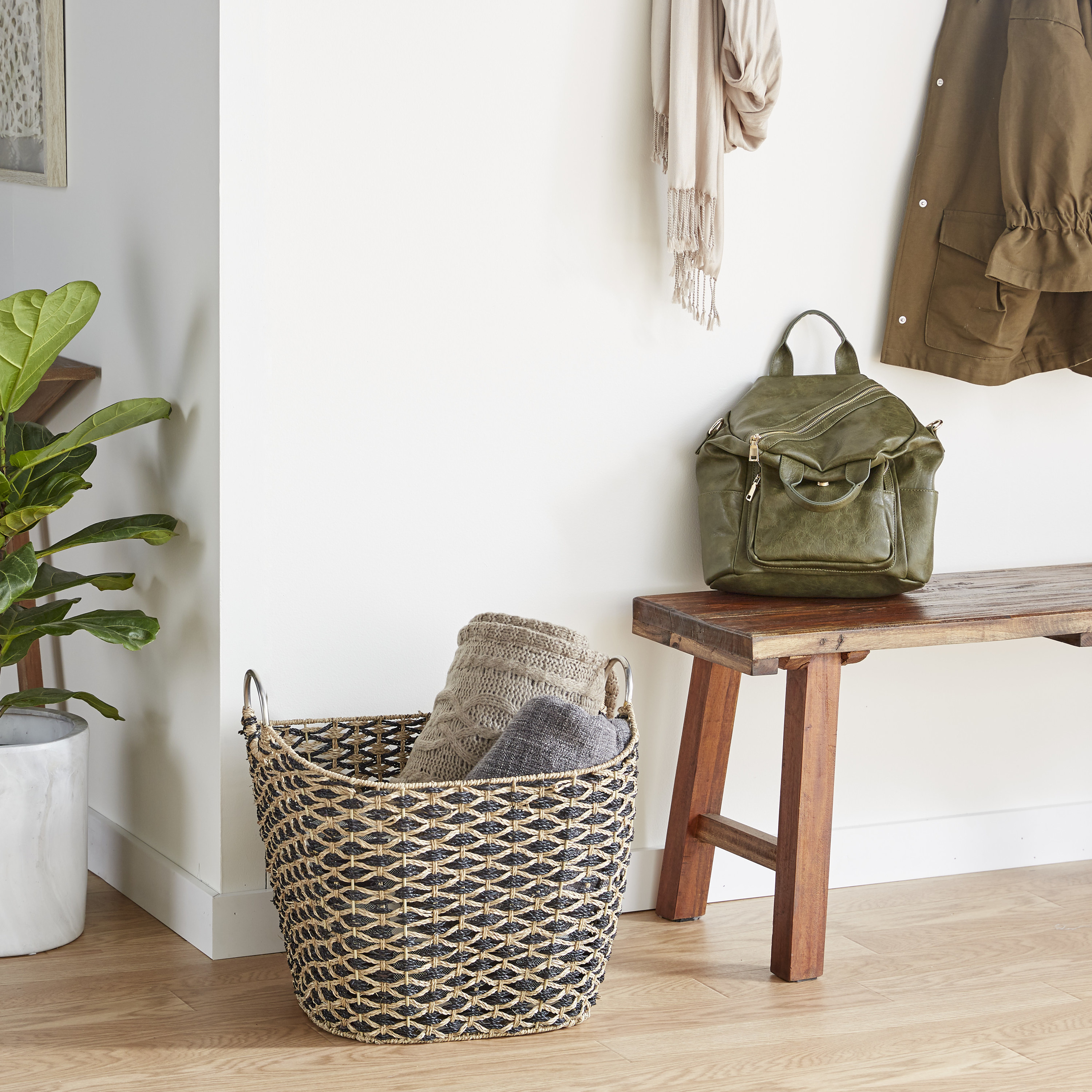 the wicker storage basket displayed next to a wooden bench with blankets inside of it