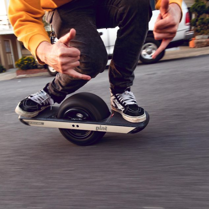A close-up of someone riding down the middle of the street on a Onewheel