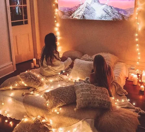 People using fairy lights during movie night