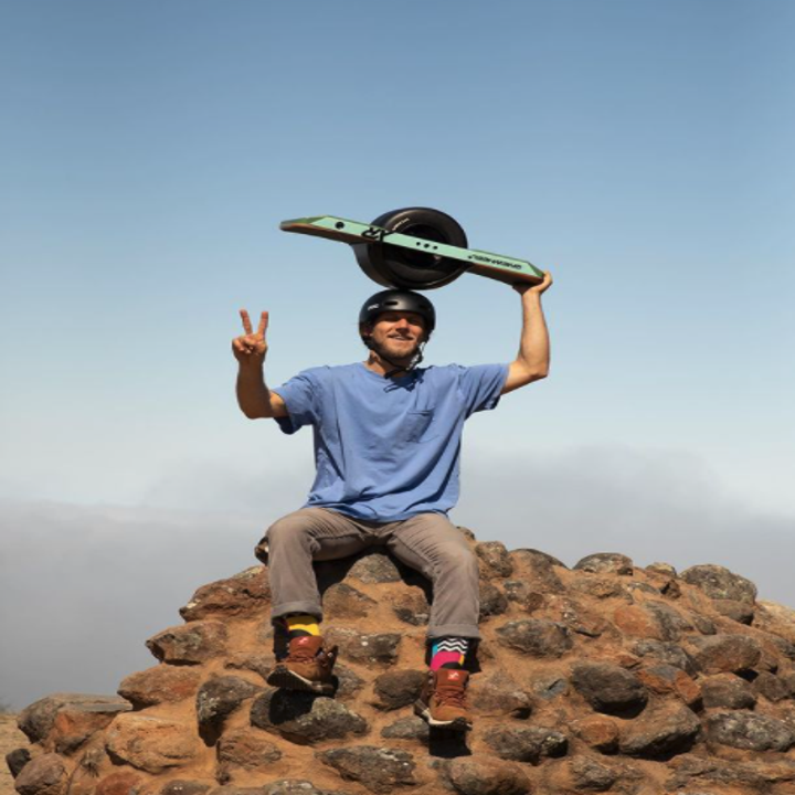 Someone sitting on the edge of a cliff while giving a peace sign and holding the Onewheel on the top of their head