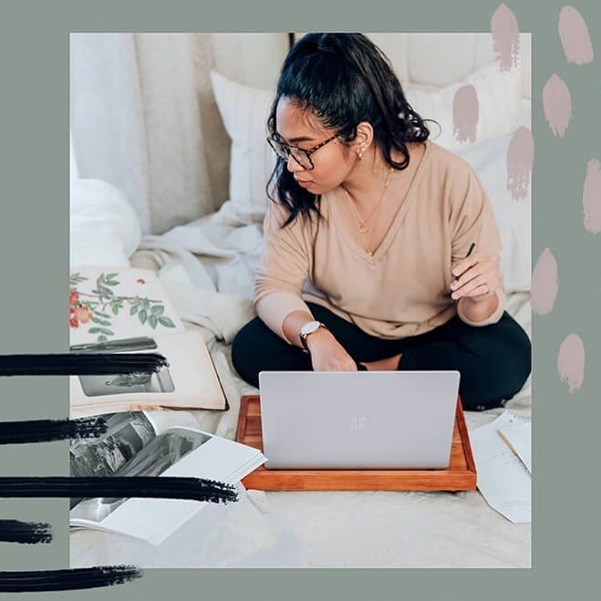 a girl on her bed, studying on her laptop with books