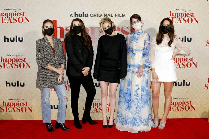 Five women stand on a red carpet for the premiere of the movie Happiest Season