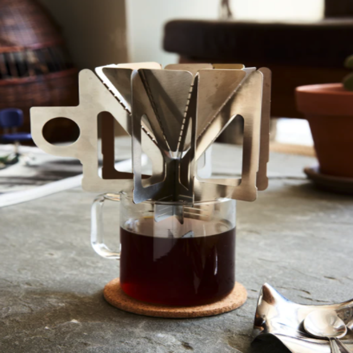 A close-up of the brewer brewing coffee into a see-through cup