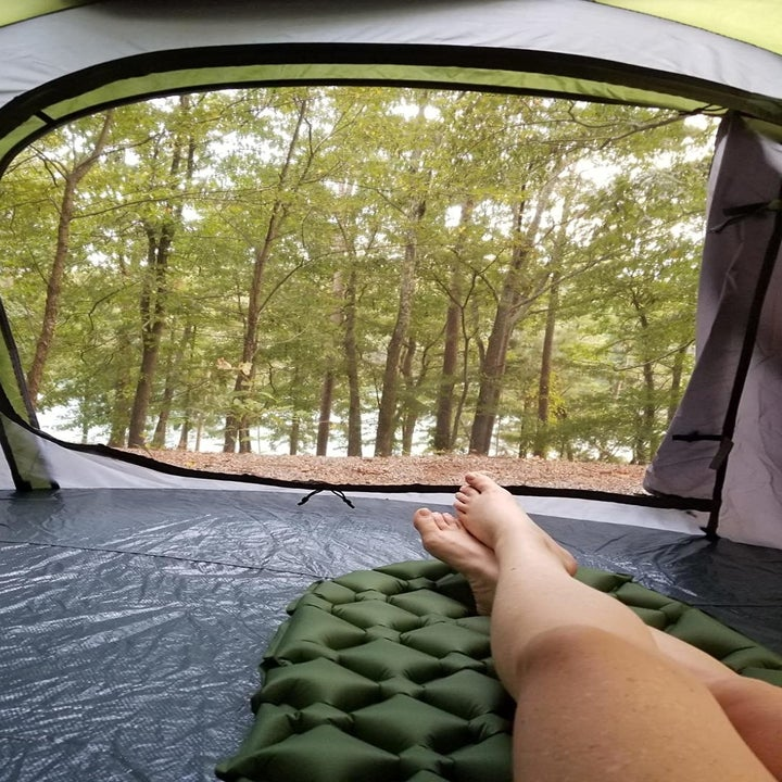 Reviewer resting on sleeping pad inside a tent