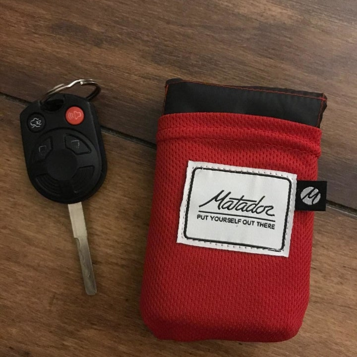 The blanket packed into a small case that is the same size as the car key beside it