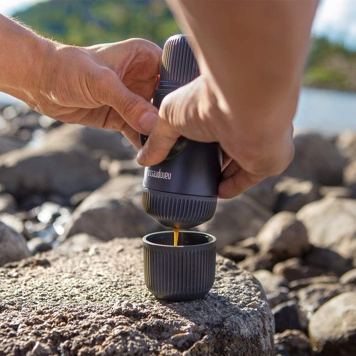 Hands pouring espresso into the lid that comes with the Nanospresso maker