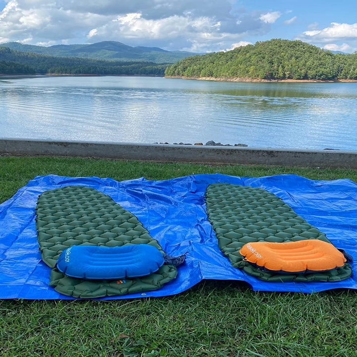 Two pads resting on grass by a lake