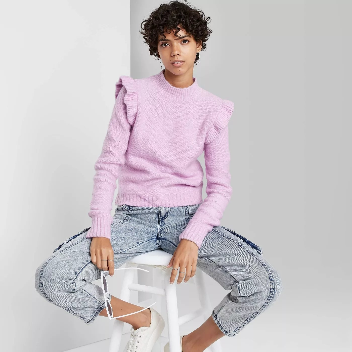A lavender ruffle sweater paired with jeans and sneakers.