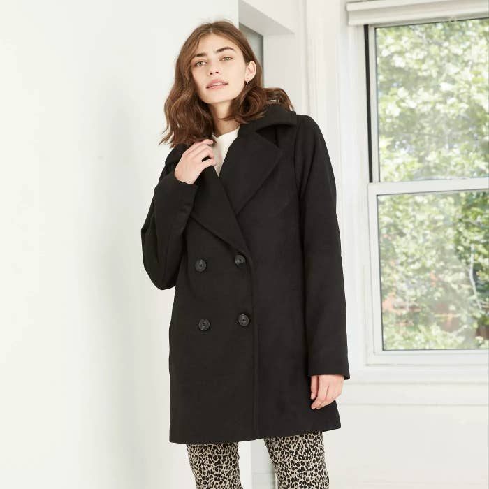 A short black coat with buttons paired with cheetah pants.
