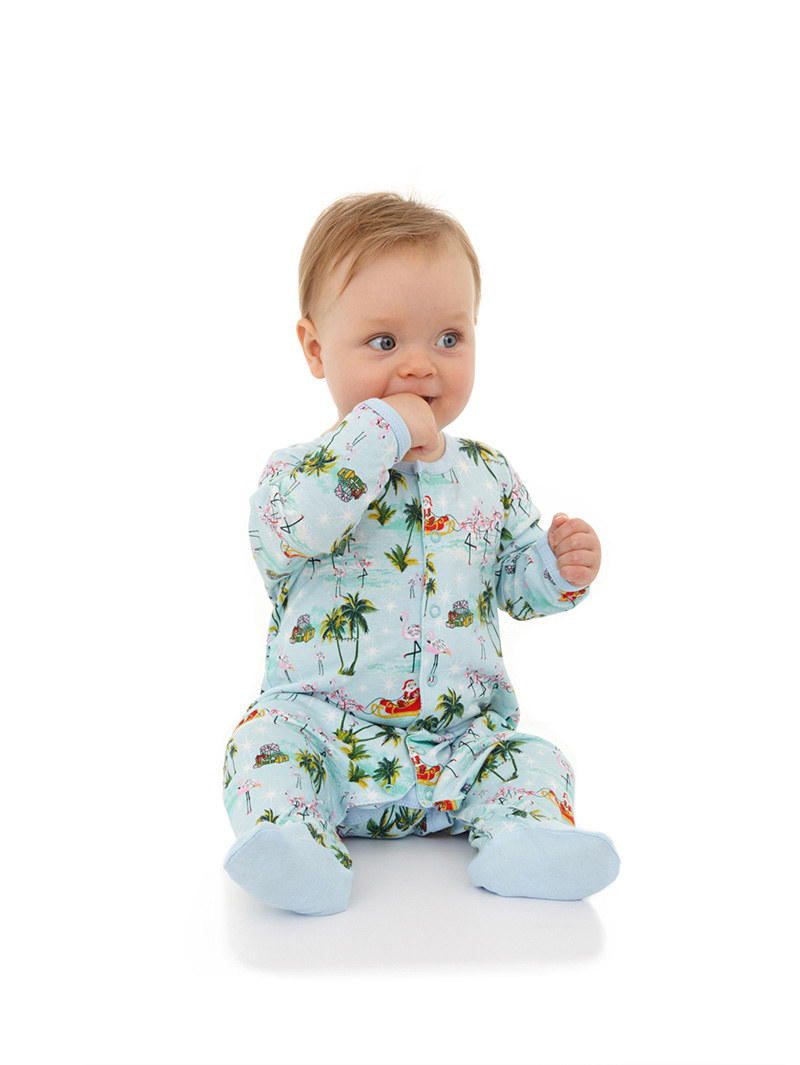 Baby in a light blue onesie with palm trees and buttons down the centre