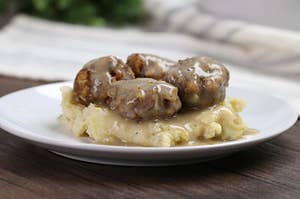 A side shot of a white plate with mash potatoes and turkey stuffing meatballs on top, covered in gravy