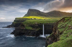 Dramatic black cliffs topped with green grass, with a waterfall dropping into a dark dea