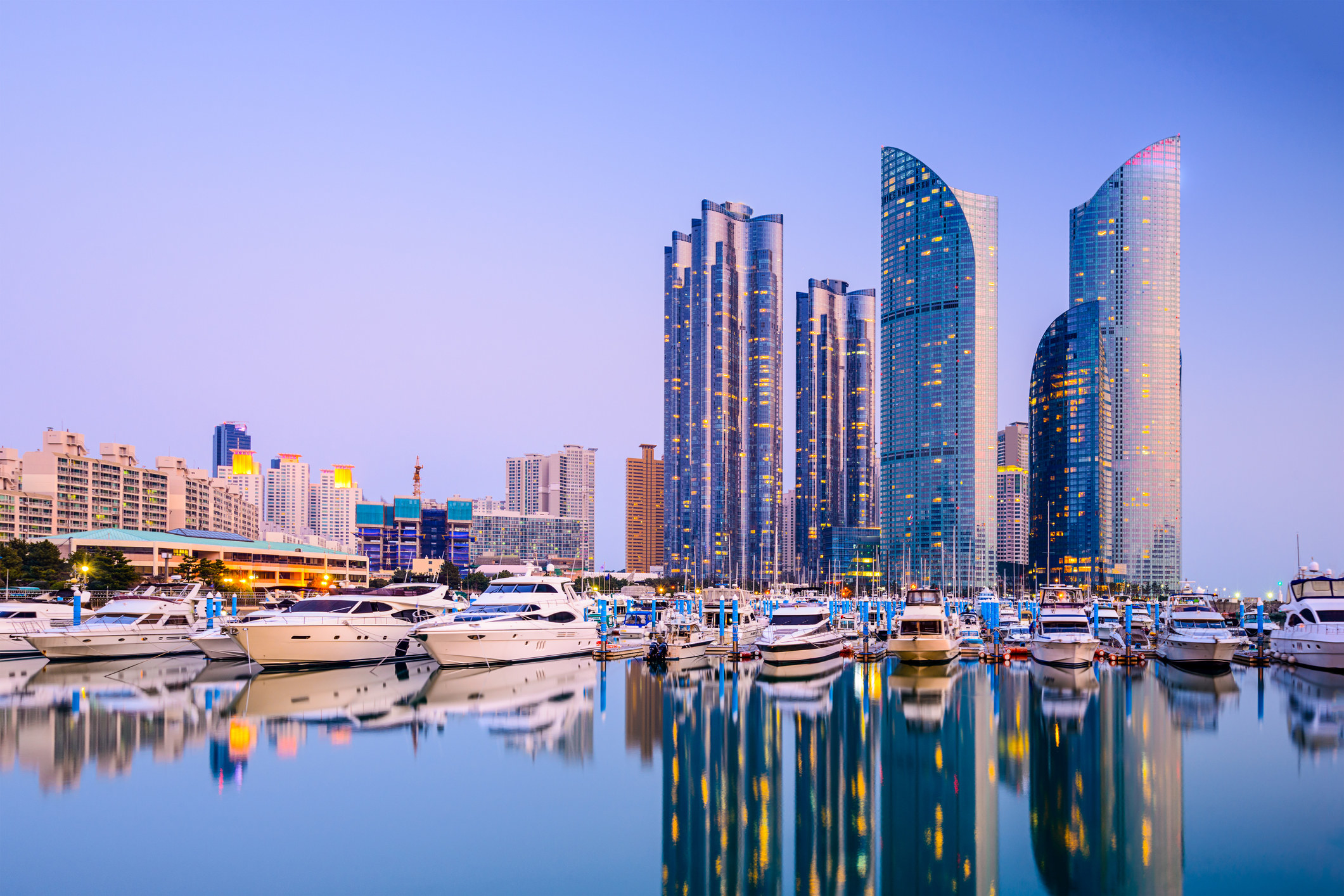 Tall skyscrapers line a harbor filled with boats at twilight