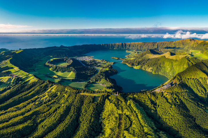 Aerial shot of a lush green island shaped like a volcano, with bright blue water in the middle