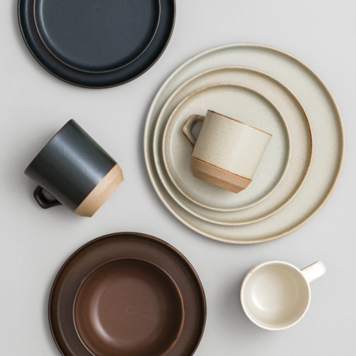 A close-up of some white and black ceramic mugs and plates from KINTO