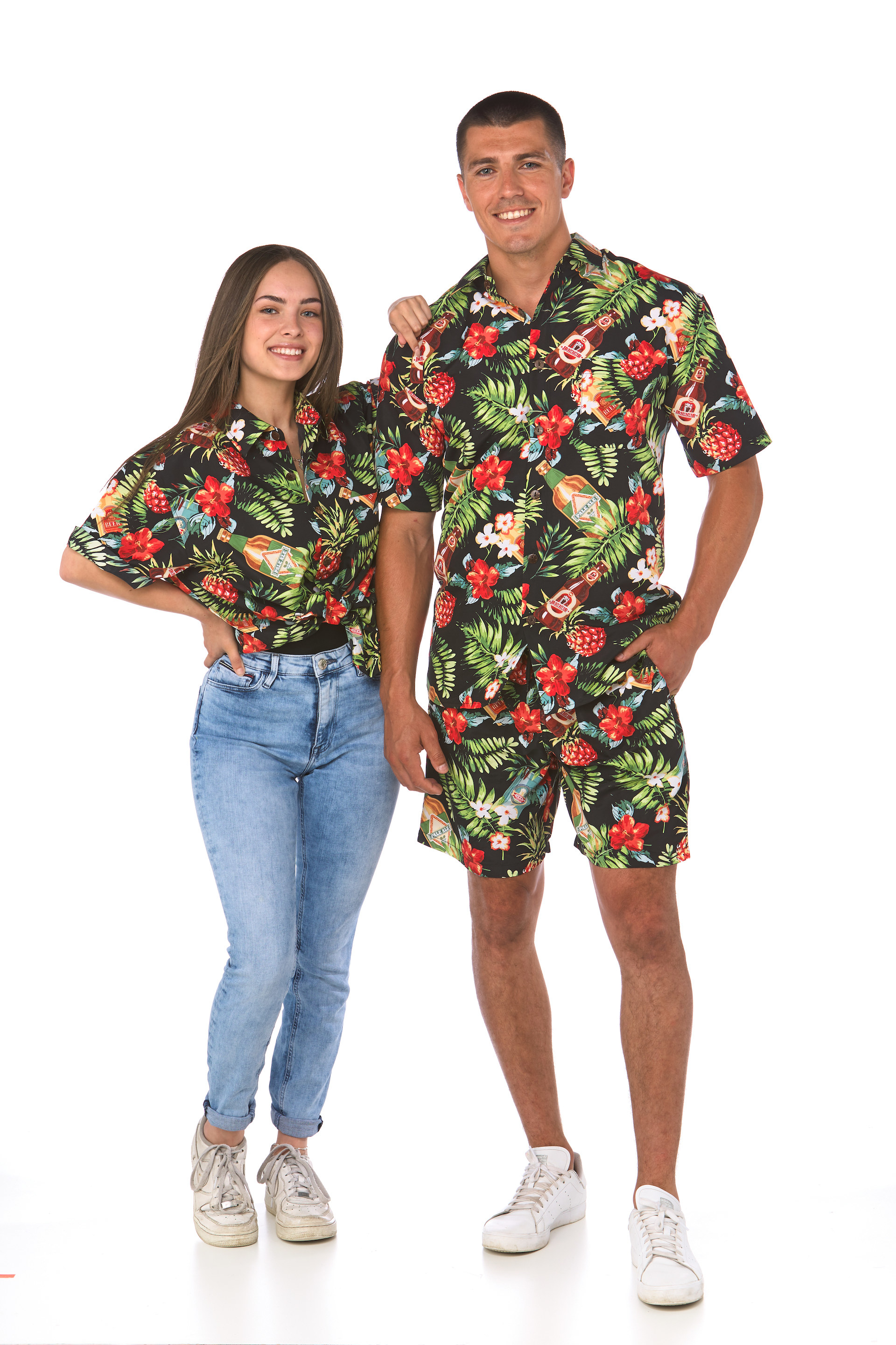 Man and woman in matching shirts with a dark background, palm fronds, flowers and beer