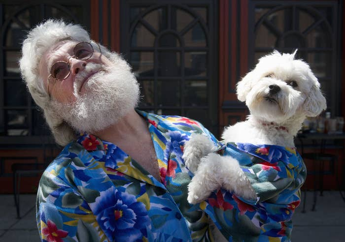 Man with white hair and beard wearing a colourful shirt and holding a dog with the same shirt