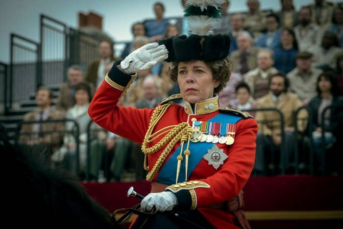 Olivia Colman as Queen Elizabeth; she is riding a horse and is doing a salute