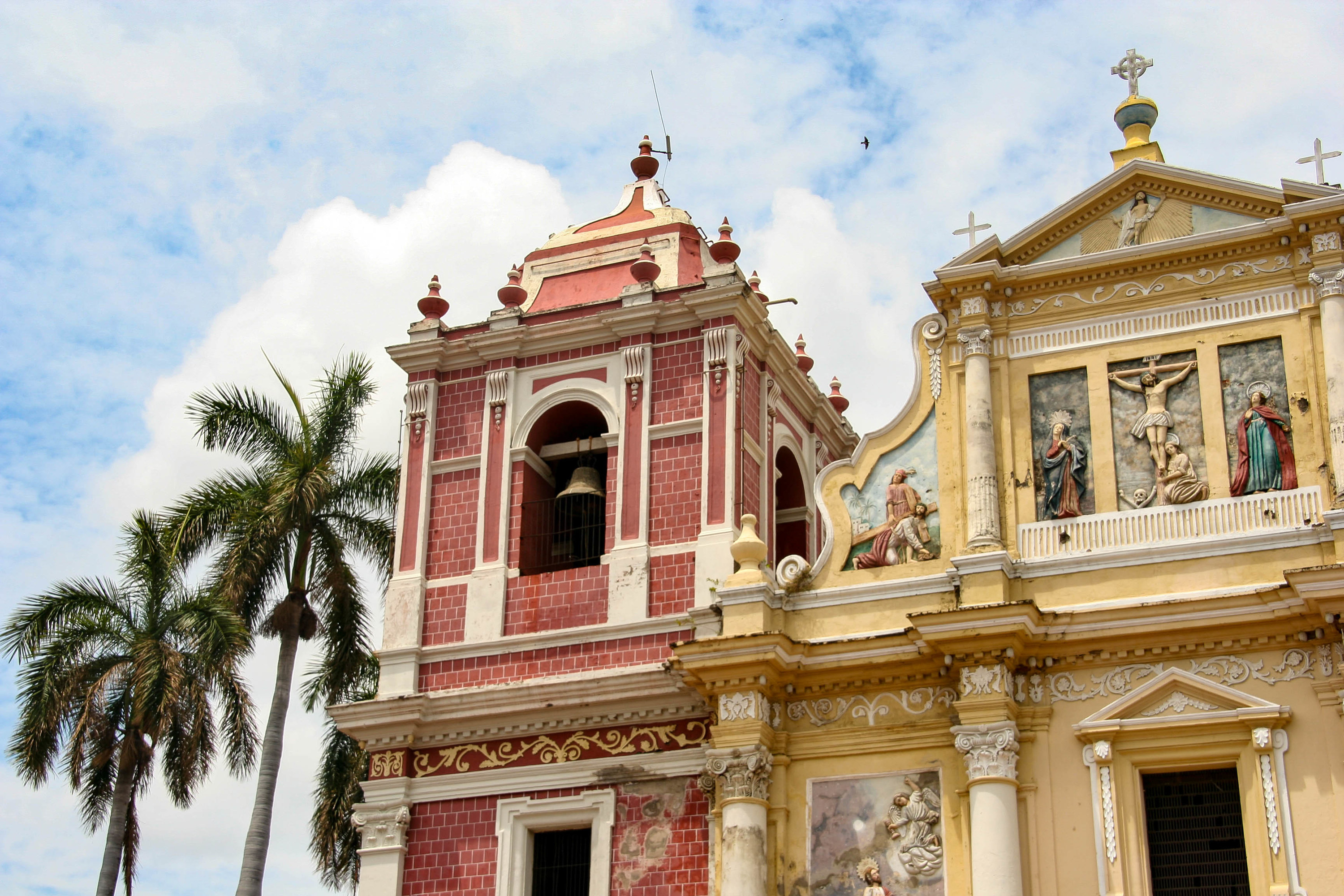 Colorful church buildings with religious art on the facade, next to two palm trees