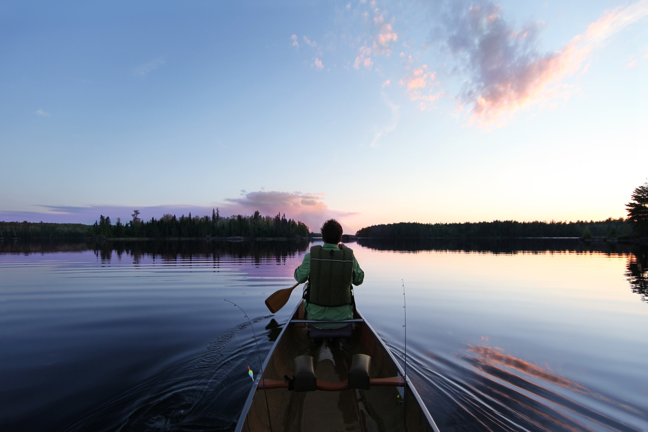 Person canoeing at dusk in flat waters