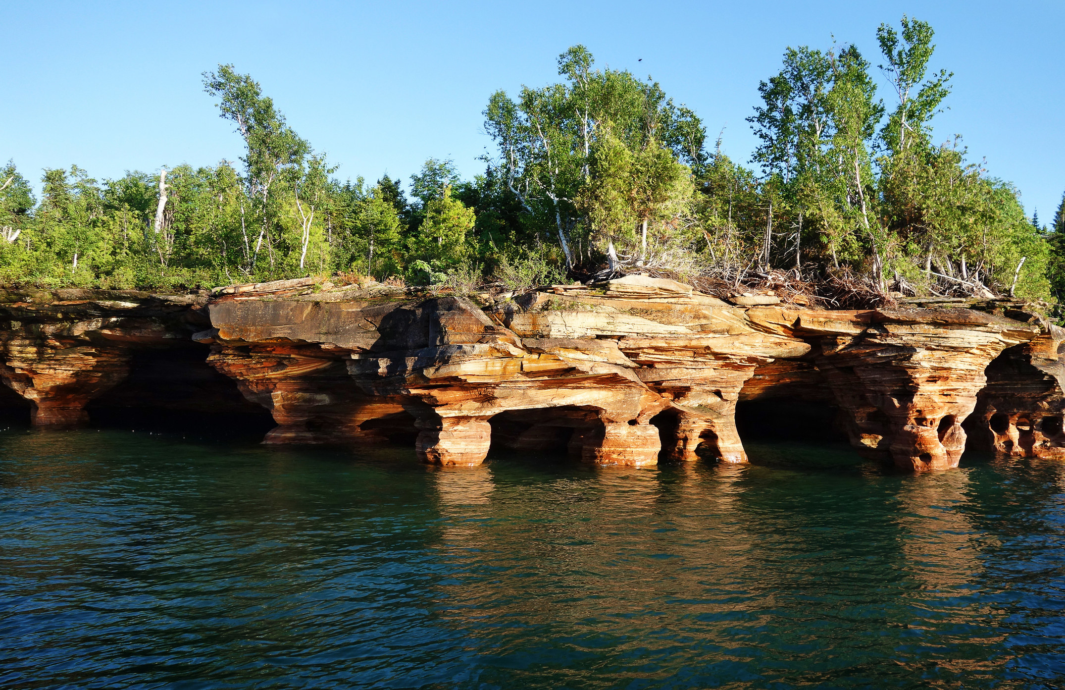 Short rocky cliffs dotted with small caves