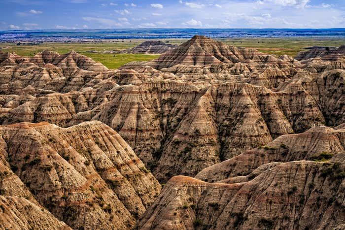 Lined rock formations leading to green plains