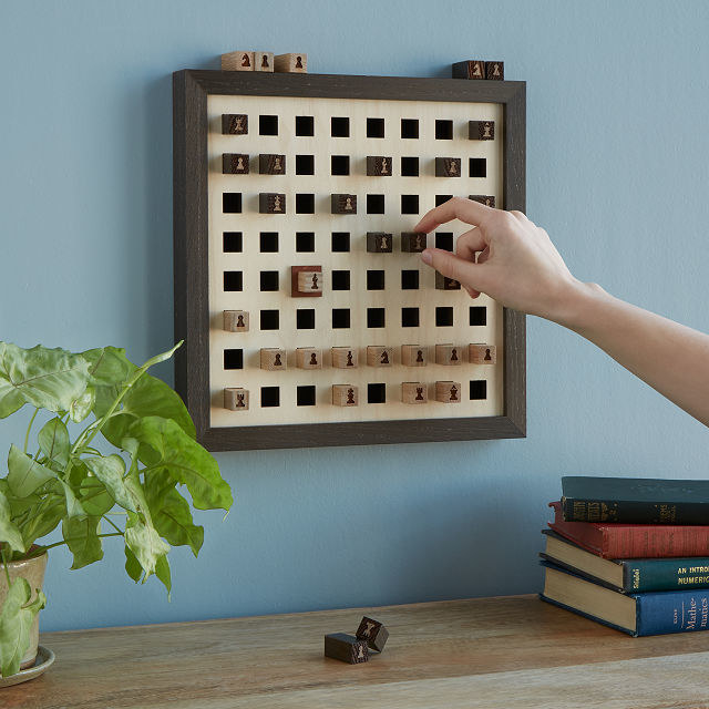 Person is moving a chess piece on a wall-mounted chess board