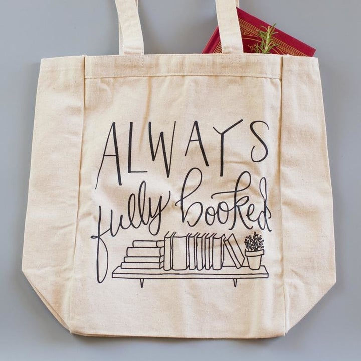 "the tote bag which says ""always fully booked"" with an illustration of books"