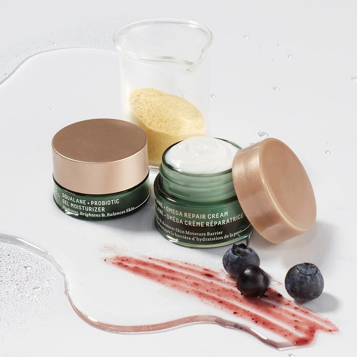 the probiotic repair cream with the lid open to show the creamy texture, with blueberries in the foreground