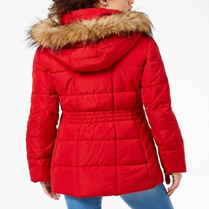 Back view of the same model wearing the puffer in red