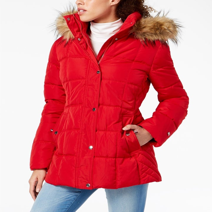 Front view of a model wearing the puffer in red