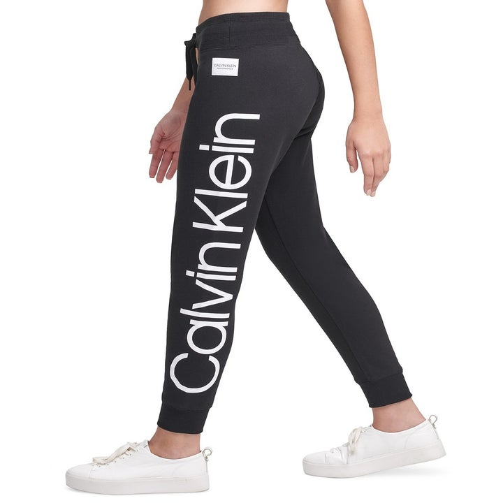 Side view of a model wearing the joggers which have Calvin Klein branding