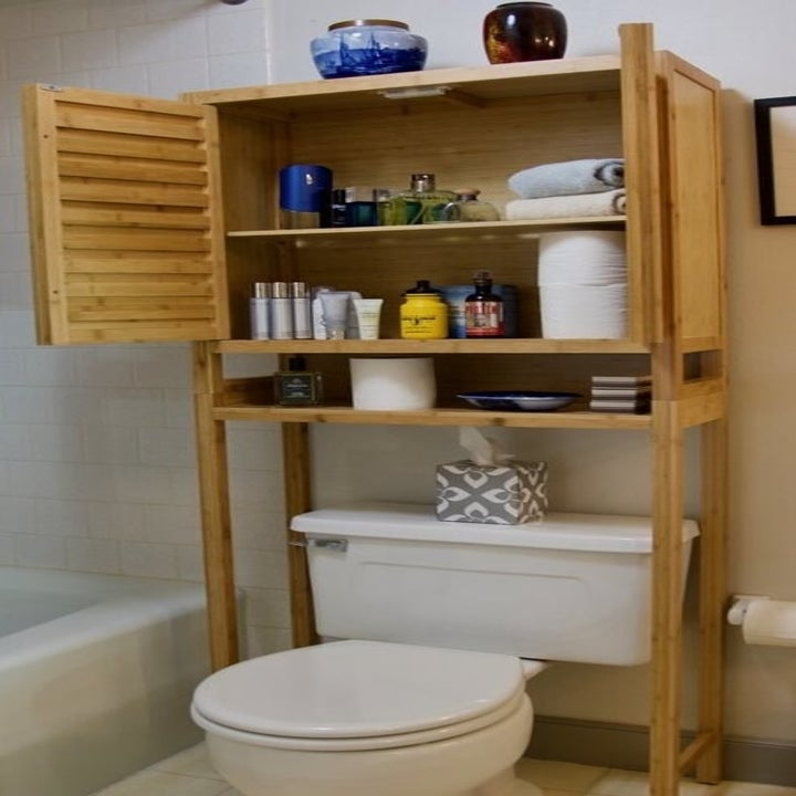 the same bay isle home mel bamboo over the toilet storage with the cabinet doors open